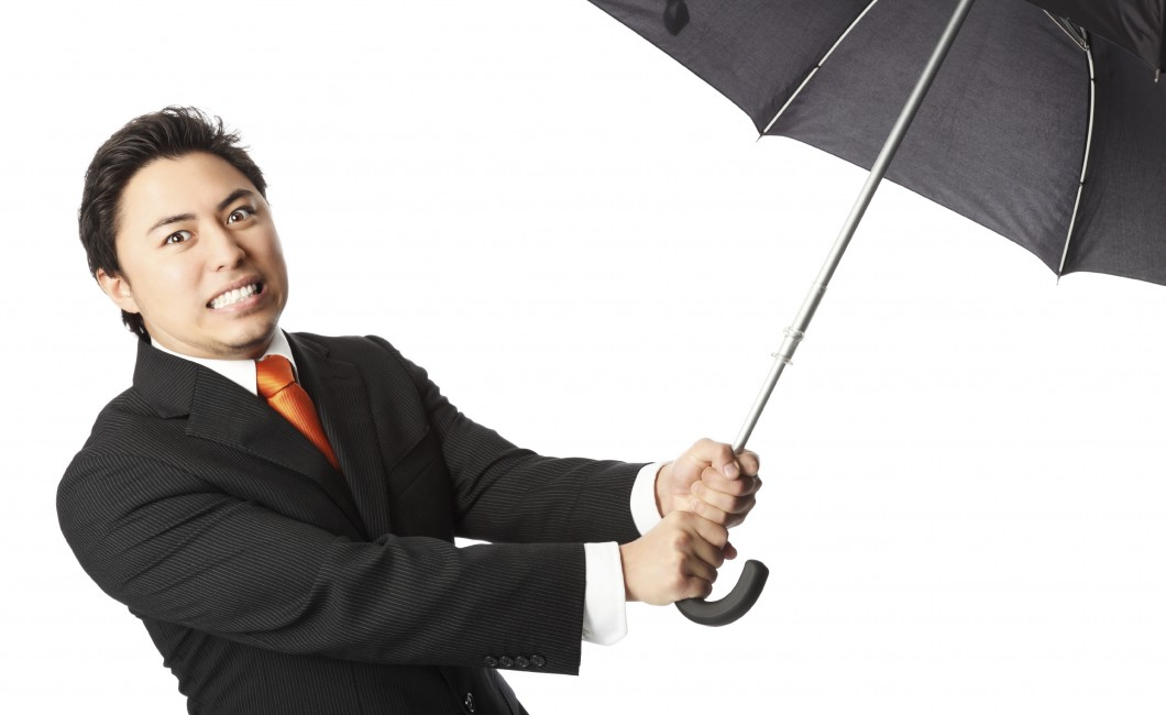 man holding an umbrella in article dealing with weather anxiety